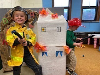 Preschool students putting out fake house fire after they learned about fire safety.