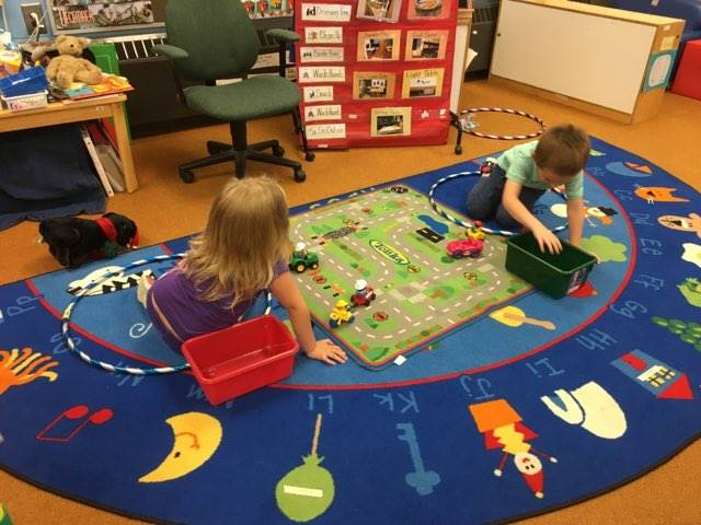 Students playing with cars