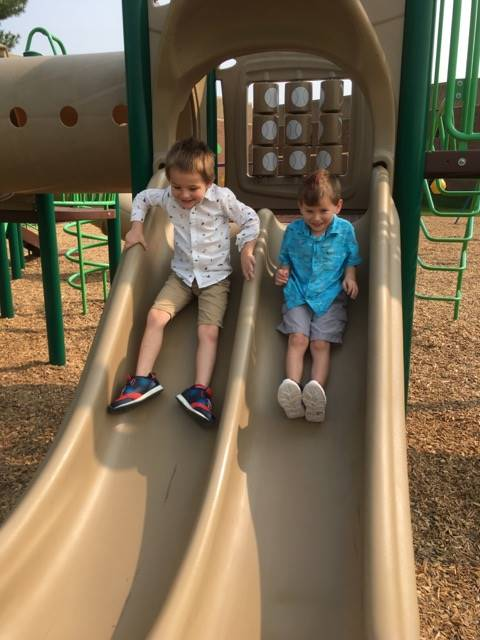 Two Students sliding down the slides