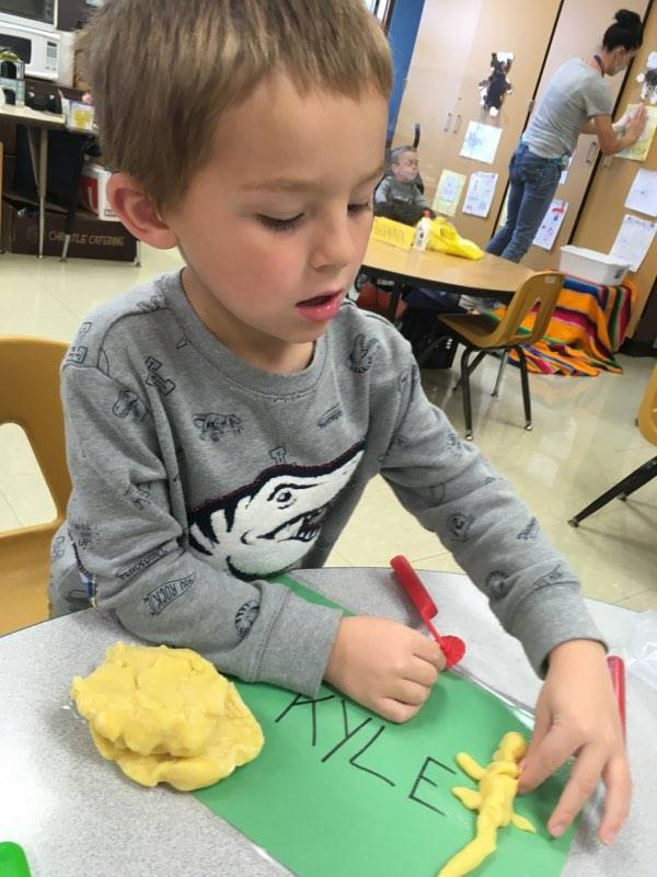 Student writing his name with playdoh