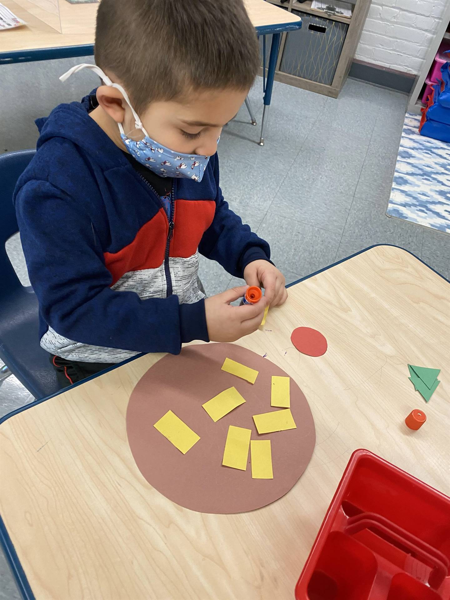 Student using yellow rectangles and other shapes to make his own pizza