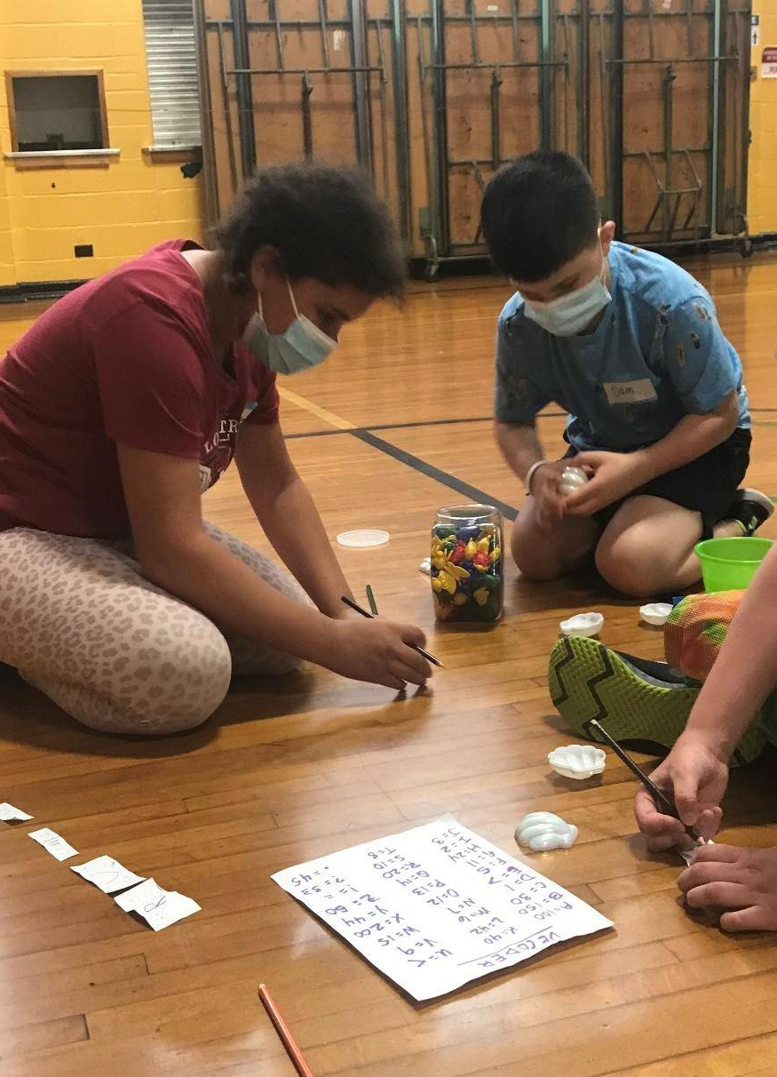 Students participating in a seashell math activity during water safety week!